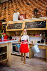 A stunning blonde with buckets in her arms standing in the kitchen