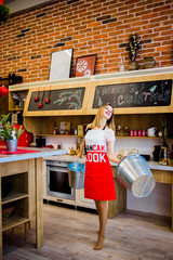 A shapely blonde with buckets in her arms standing in the kitchen