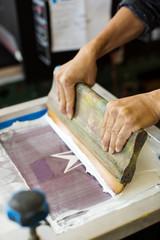 Cropped image of worker pressing ink on frame in workshop