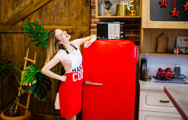 The sweet girl in an apron is in the kitchen near the red refrigerator