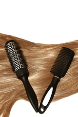 Woman hair styling with a brush and a comb