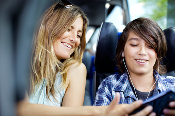 Cheerful mother and son using mobile phone while sitting in bus