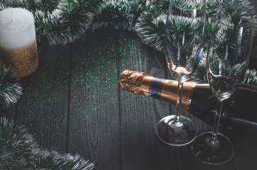A bottle of champagne and two glasses stand on a dark gray wooden table surrounded by Christmas decorations
