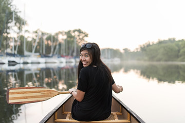 young woman sitting in canoe