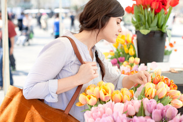 Side view of woman shopping for tulip flower at flower shop
