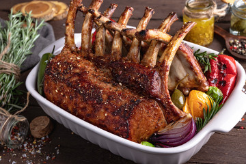 Grilled roasted rack of lamb chops with vegetables, in ceramic baking dish