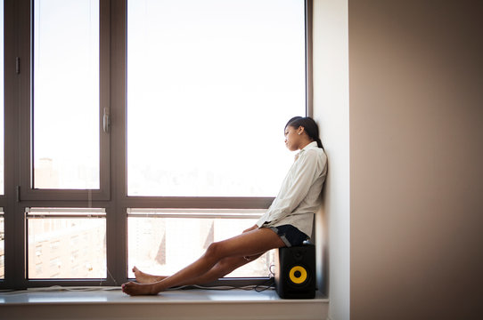 Side view of woman sitting on speaker by window at home
