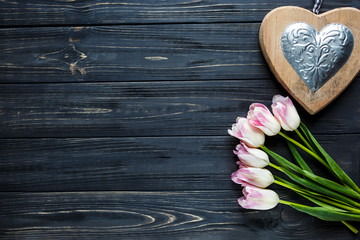 colorful beautiful tulips and decor as a heart on the gray wooden table. Valentines, spring background. floral mock up.  with copyspace. happy mothers day, romantic still life, fresh flowers