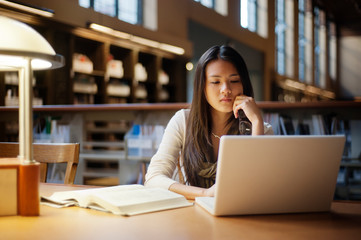 Woman using laptop computer while sitting in library