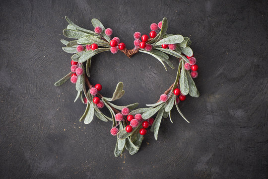 Christmas decorative heart made from red mistletoe berries and leaves on dark