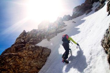Low angle view of man climbing snow covered mountain