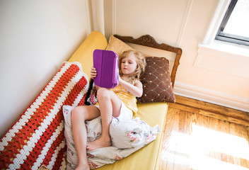 High angle view of girl using tablet computer while lying on sofa