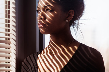 Woman looking away while standing by blinds at home
