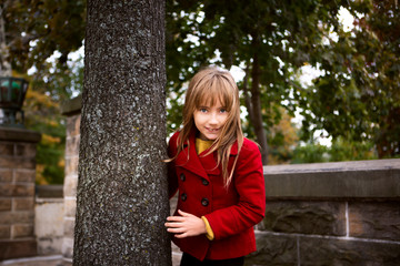 Portrait of happy girl standing by tree trunk in park