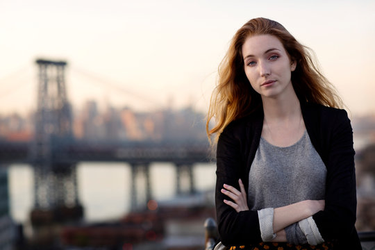 Portrait of confident woman with arms crossed standing on tarries against Williamsburg bridge