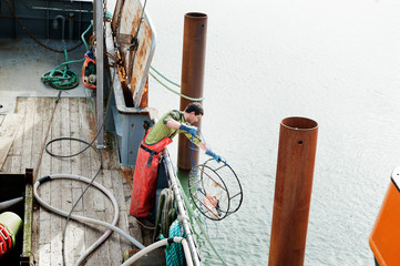 High angle view of fisherman putting crab cage on fishing boat at sea