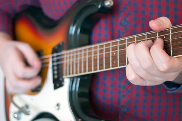 Hands of a man in a plaid shirt playing vintage sunburst guitar