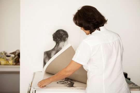 Rear view of woman looking at paintings while standing at studio