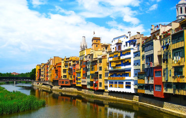 Colorful yellow and orange houses  reflected in water river , in Girona, Catalonia, Spain. Church Saint Mary Cathedral at background