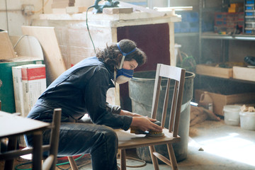Side view of female carpenter sanding wooden chair at workshop
