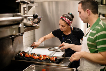 Chef preparing food at barbeque grill at commercial kitchen