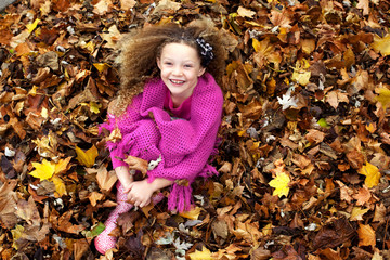 Portrait of cheerful girl sitting on field covered with dry leaves
