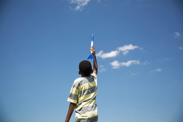 Low angle view of boy holding model rocket against blue sky