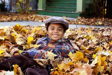 Portrait of happy boy lying on fallen dry leaves