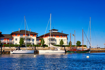 Holiday apartments with sailing boats in the harbor Weiße Wiek.