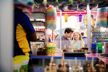 Couple looking at chocolate lollipops while standing outside stall in amusement park