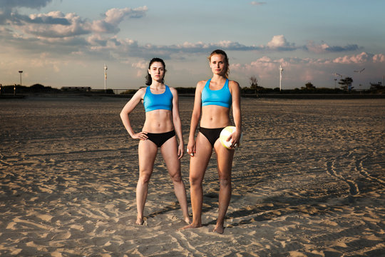 Confident women standing at beach against sky during sunset