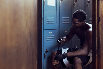 Man removing bandage while sitting in locker room