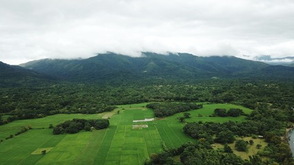 Aerial view of patchwork field and lush greenery of countryside with hills on the background in Zambales, Philippines