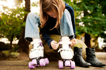 Girl putting on roller skates while sitting on rock