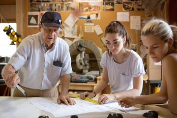 Senior man explaining plan to women while working in workshop