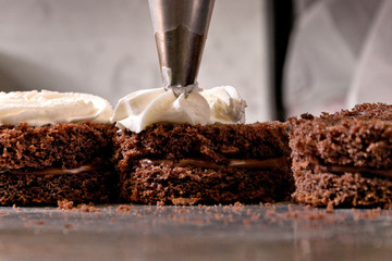 Cropped image of icing bag decorating chocolate sponge cakes at counter