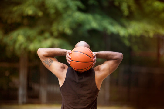 Rear view of man throwing basket ball in court
