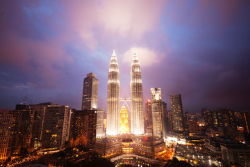Illuminated PETRONAS Towers against dramatic sky