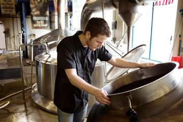 Man looking at storage tank at brewery