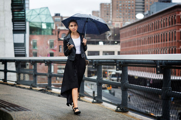 Front view of woman carrying umbrella while walking on bridge in city