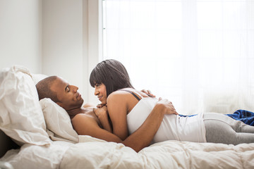Man embracing woman while lying on bed at home