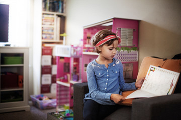 Girl reading book while sitting on sofa at home
