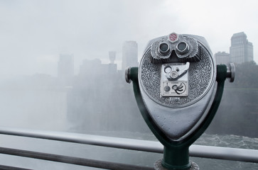 Coin-operated binoculars against river in city during rain