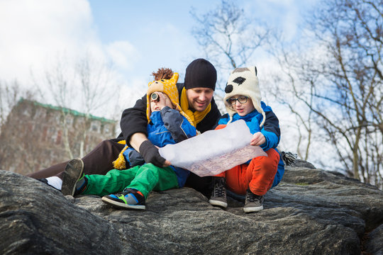Father with boys reading map while sitting on rock against sky