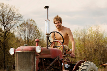 Portrait of happy farmer sitting on tractor against sky