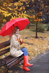 Woman with umbrella sitting on bench in autumn park. Rainy day