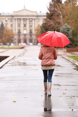 Woman with umbrella taking autumn walk in city on rainy day