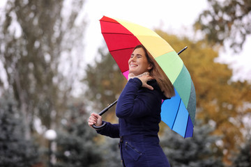 Woman with umbrella in autumn park on rainy day