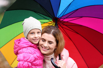 Mother and daughter with umbrella outdoors on autumn rainy day