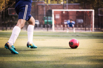 Cropped image of man kicking ball at field